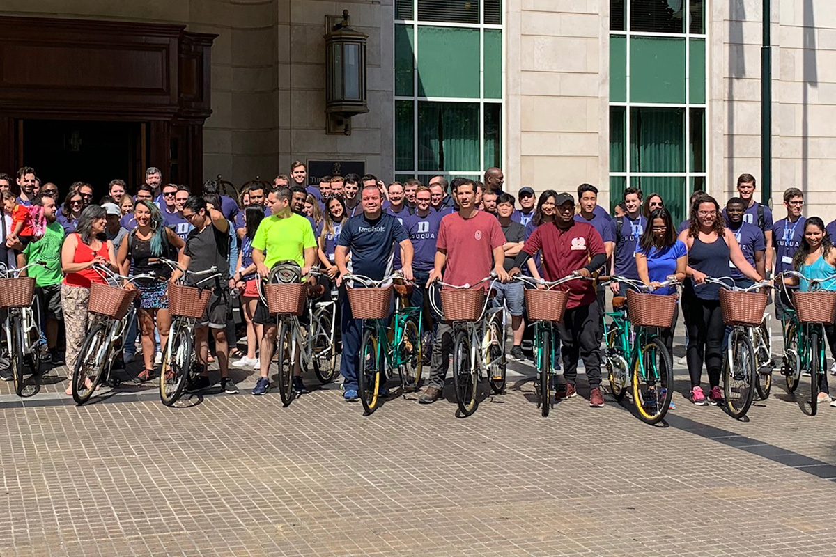 dozens of students pose alongside bikes that were built during a team building exercise, international student