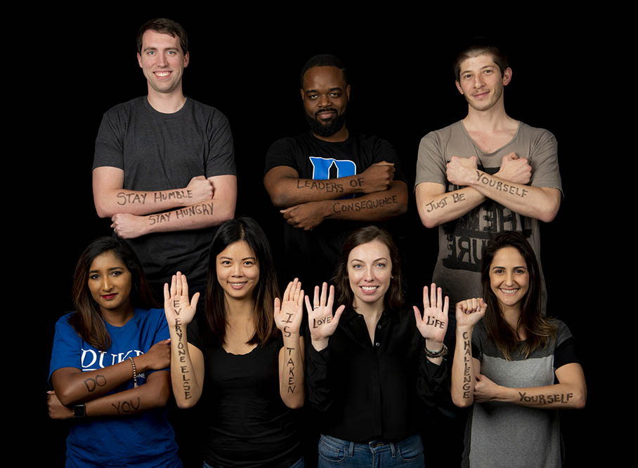 seven students, with inspirational quotes written on their hands and arms, pose for a photo; key learnings