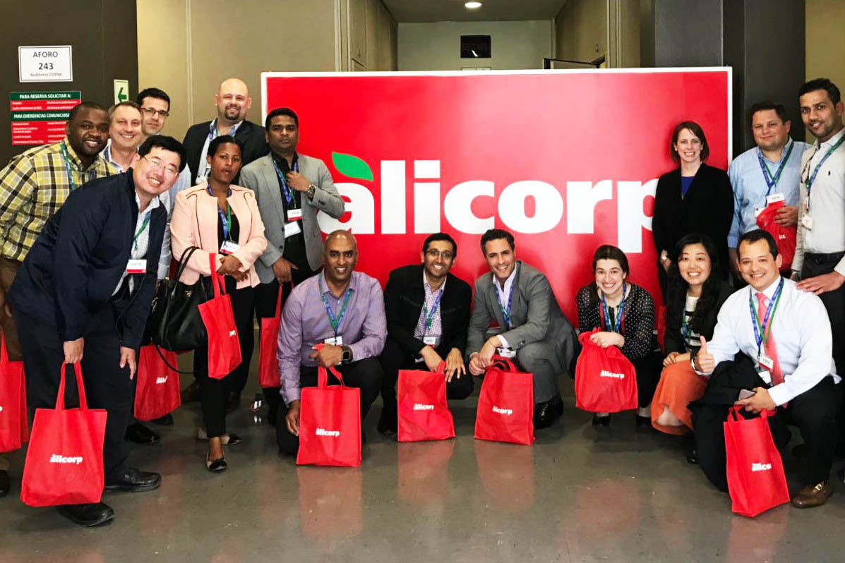 15 students pose in front of an Alicorp sign with Alicorp swag bags in hand; start an MBA