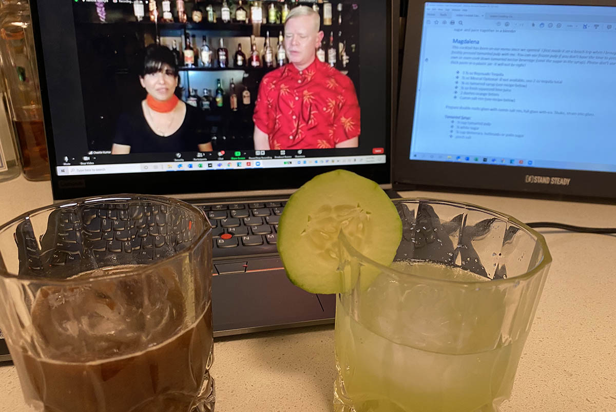 A picture of a computer screen with two people on it, and mixed drinks in the foreground; creating cultural immersion