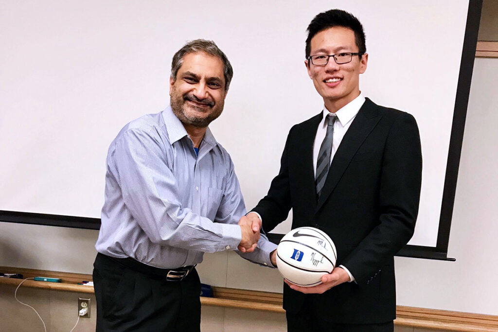 A judge presenting Xin the prize for winning the case competition, a signed Coach K basketball