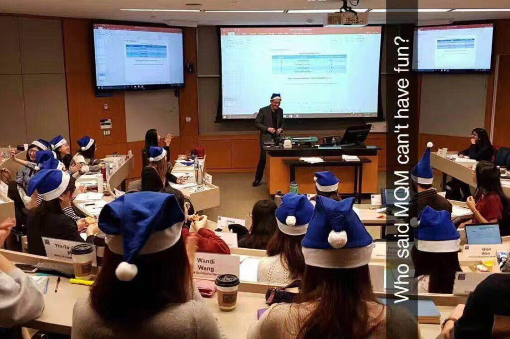 students and their professor in class wearing Duke Santa hats, extracurricular activities