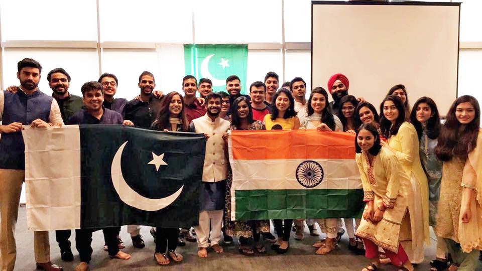 Two dozen students pose behind Indian and Pakistani flags, symbolic of student diversity at Fuqua
