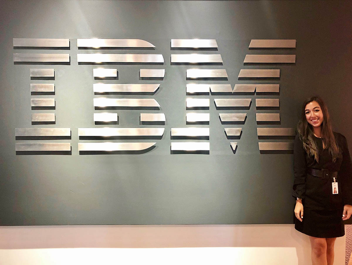 Bella standing beside an IBM sign at her office, one of cohort's employment outcomes