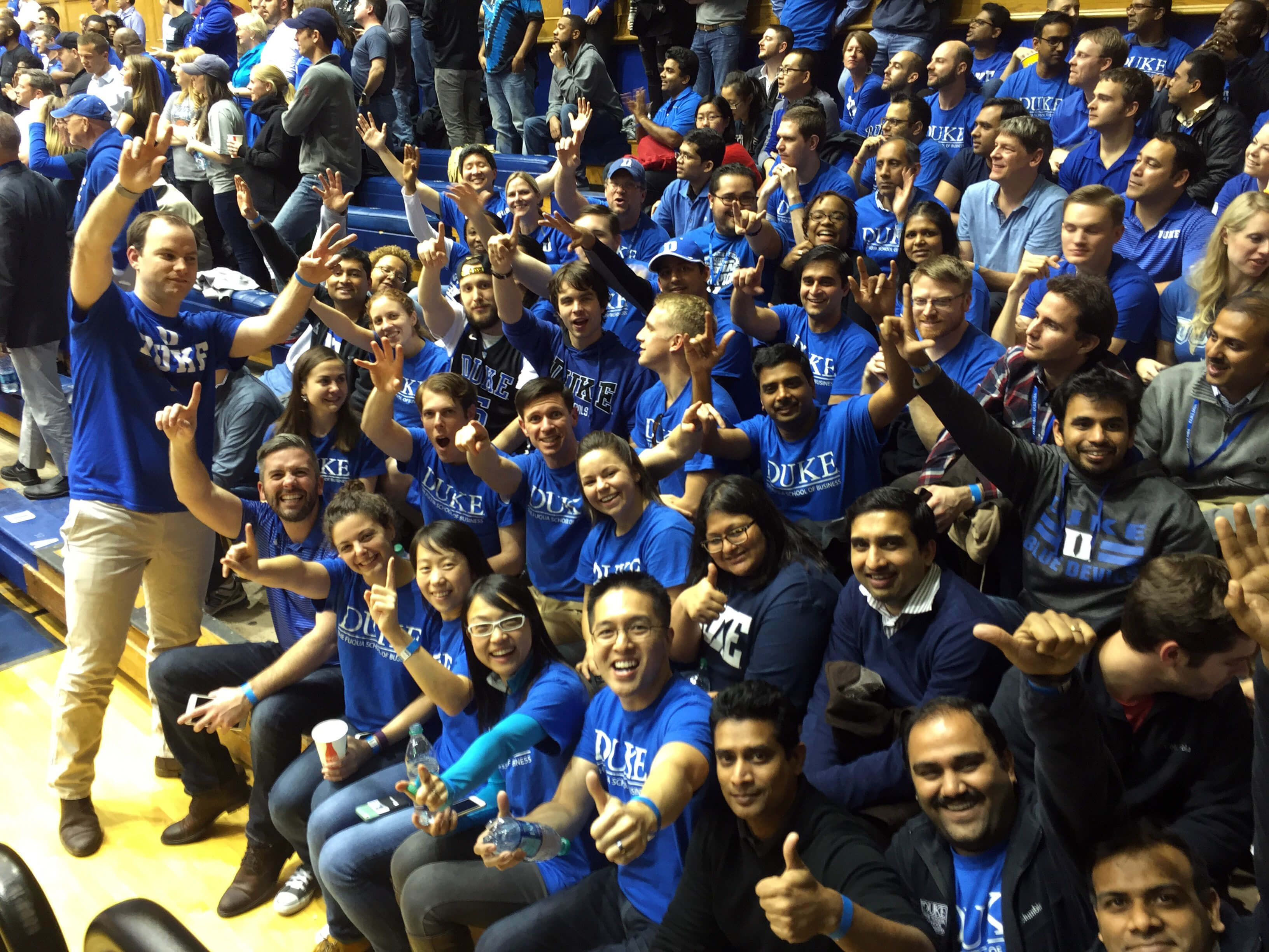 dozens of students sitting in the stands at a basketball game in Cameron Indoor Stadium, a scene unique to the MBA experience at Duke