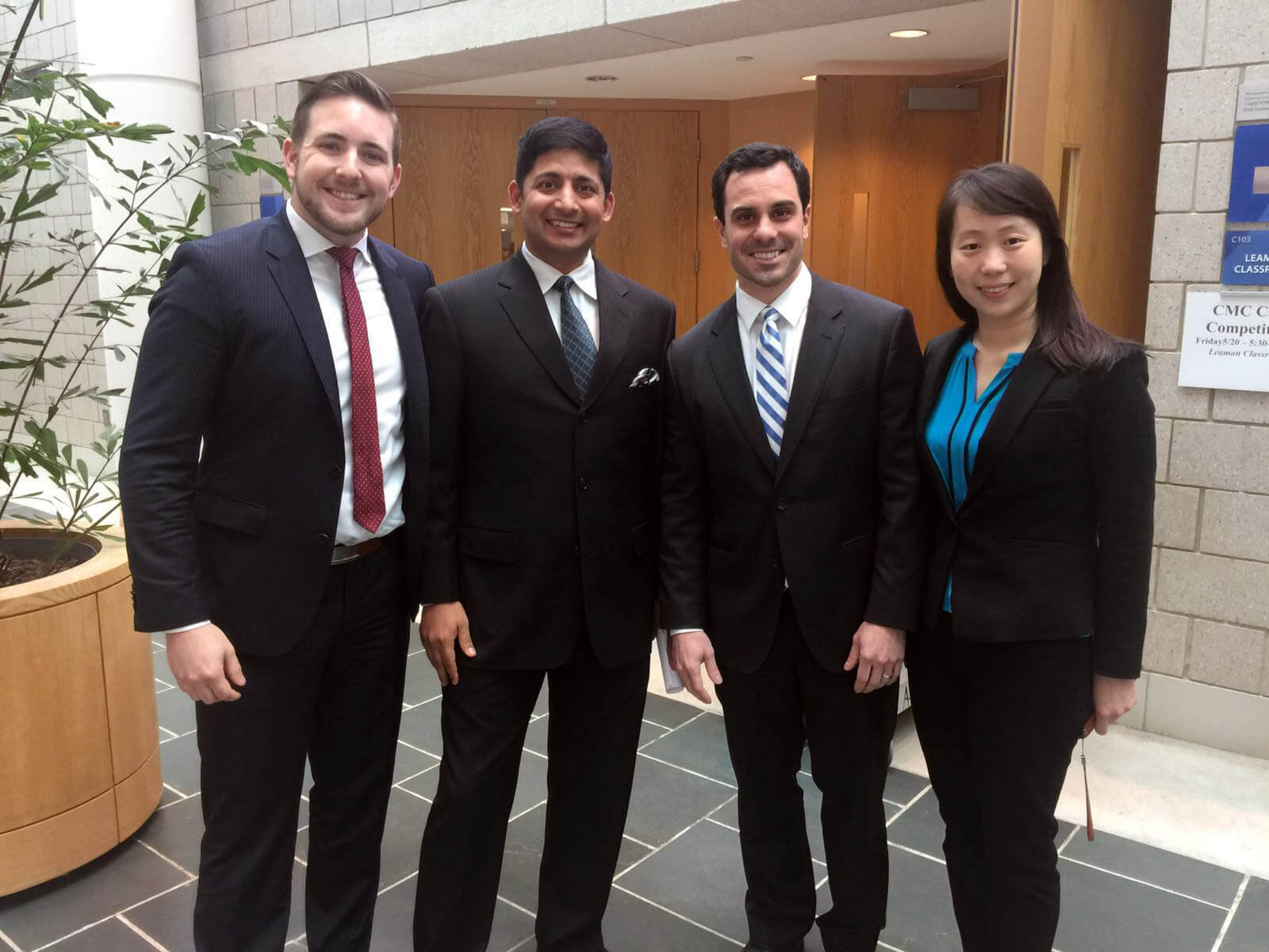 the 4 team members in suits after the case competition presentation