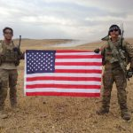 Me and a fellow veteran holding a U.S. flag during their military experience