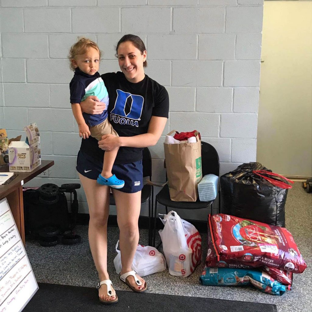 Marina with her young child, collecting hurricane relief supplies