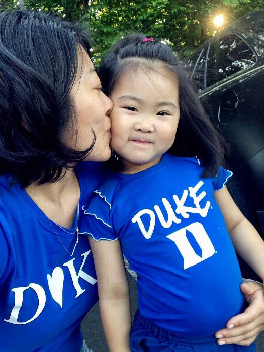Jiazi kissing Kiera, both wearing Duke T-shirts, part of life as a single parent in an MBA program