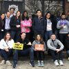 Around 15 students pose for a photo, some holding humorous signs, outside an escape room facility; Reflections 6 Months into the Weekend Executive MBA Program