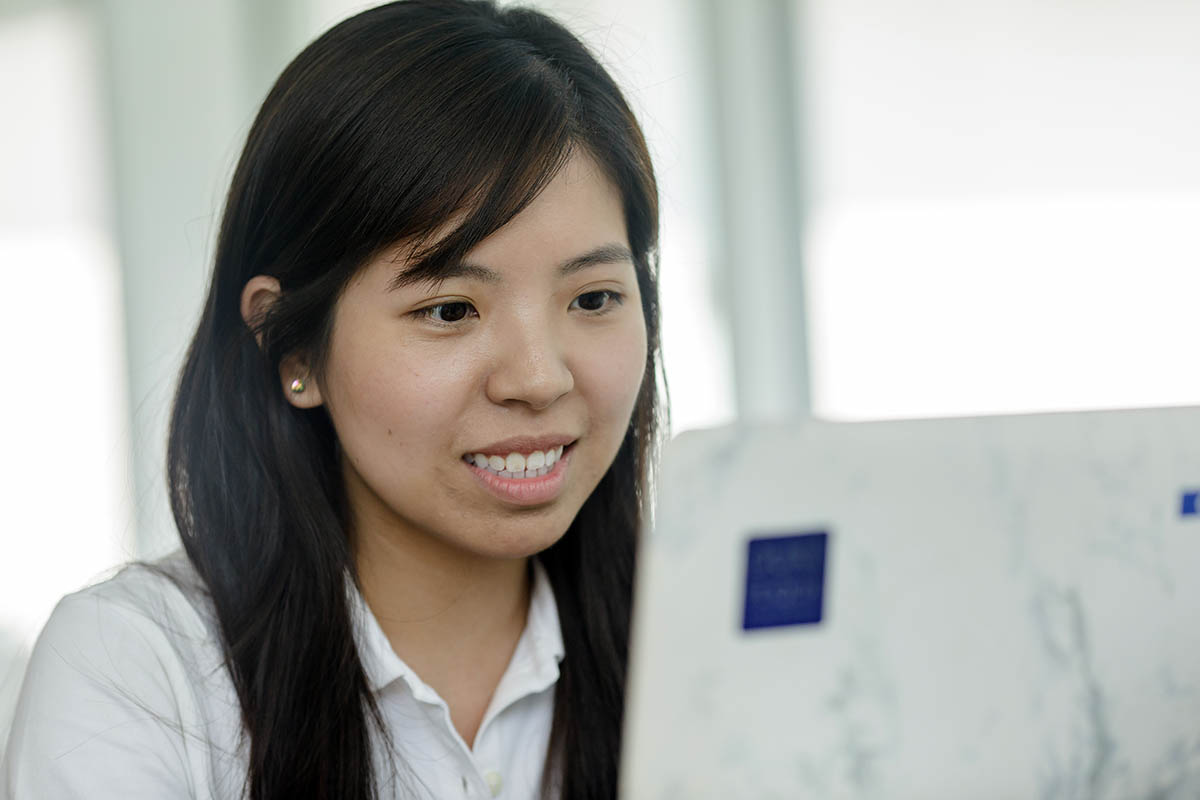 a student looking at her laptop smiling during virtual recruiting