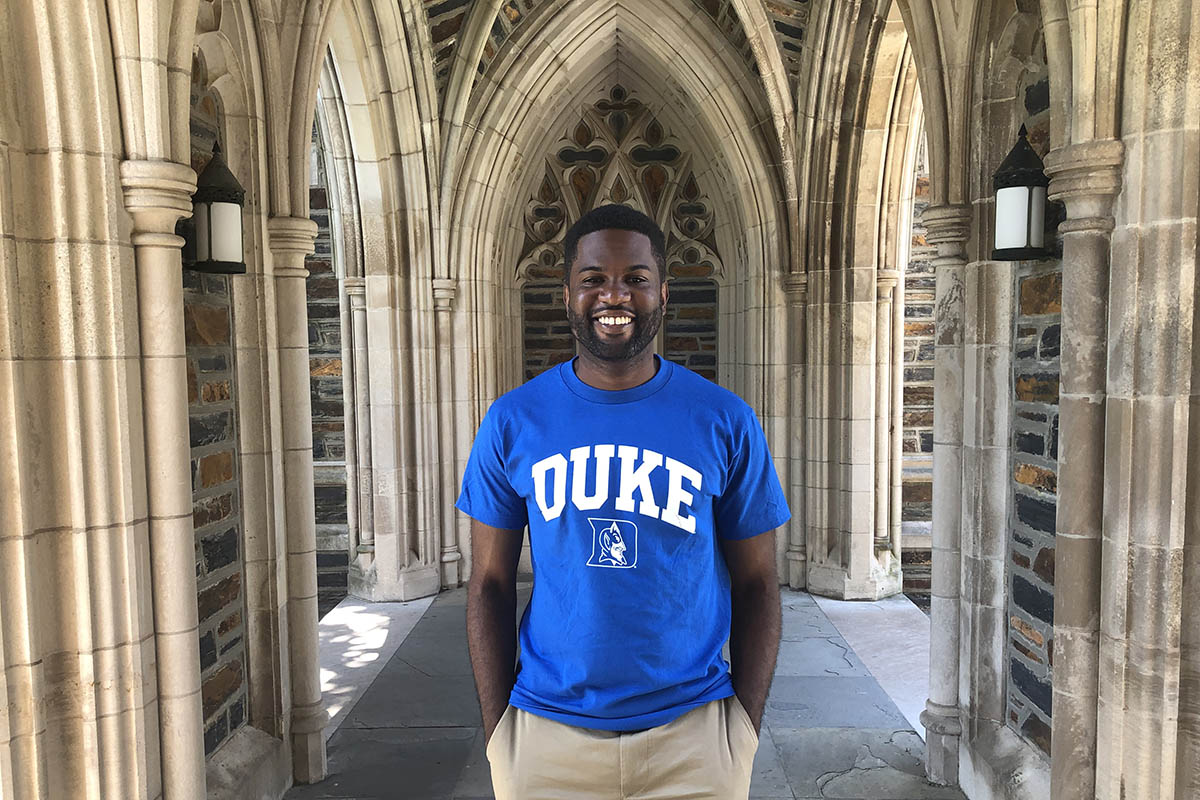 Charles on Duke campus with gothic architecture surrounding him; Fuqua's supportive minority community