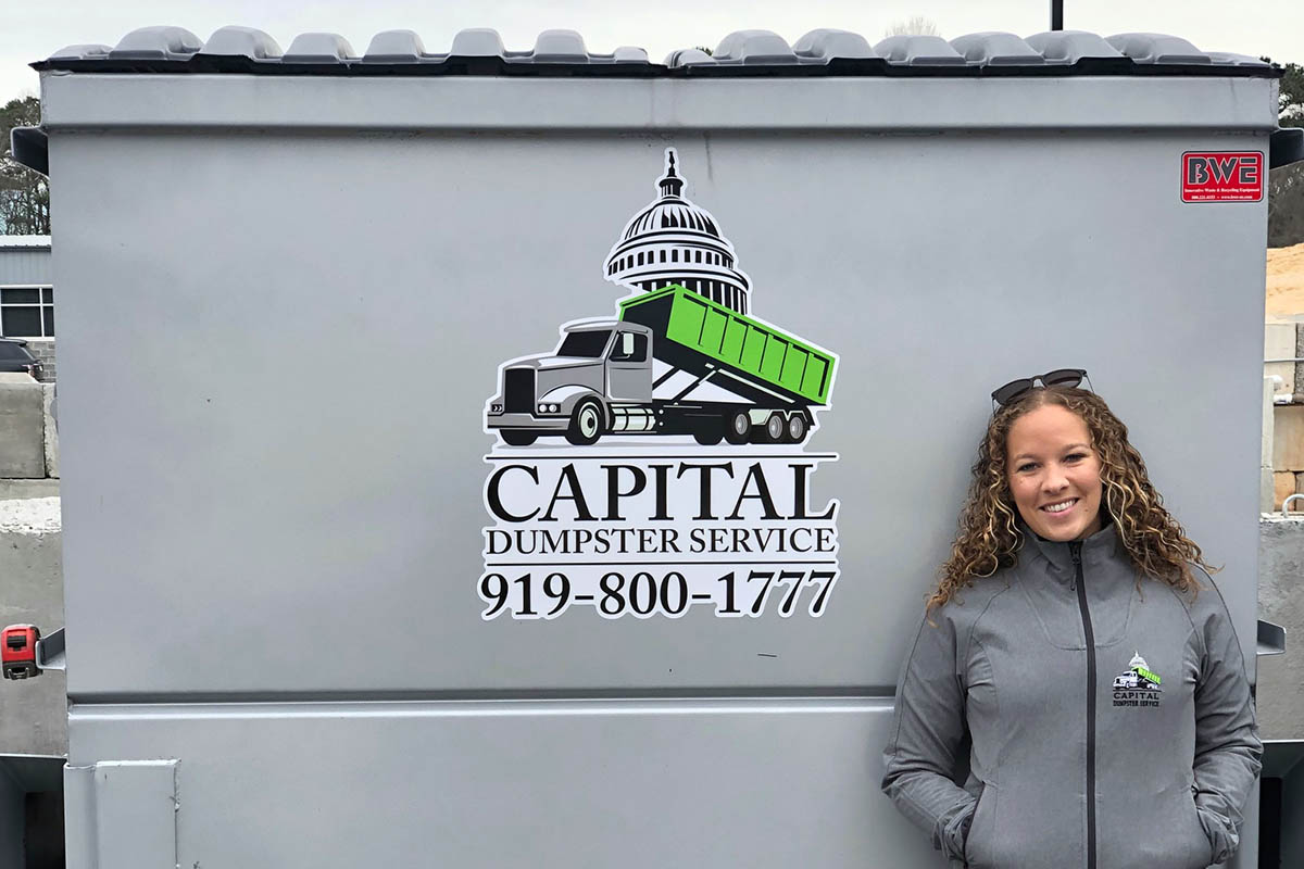 Sara standing beside one of her company's dumpsters with the logo on it and her jacket, managing an EMBA as a business owner
