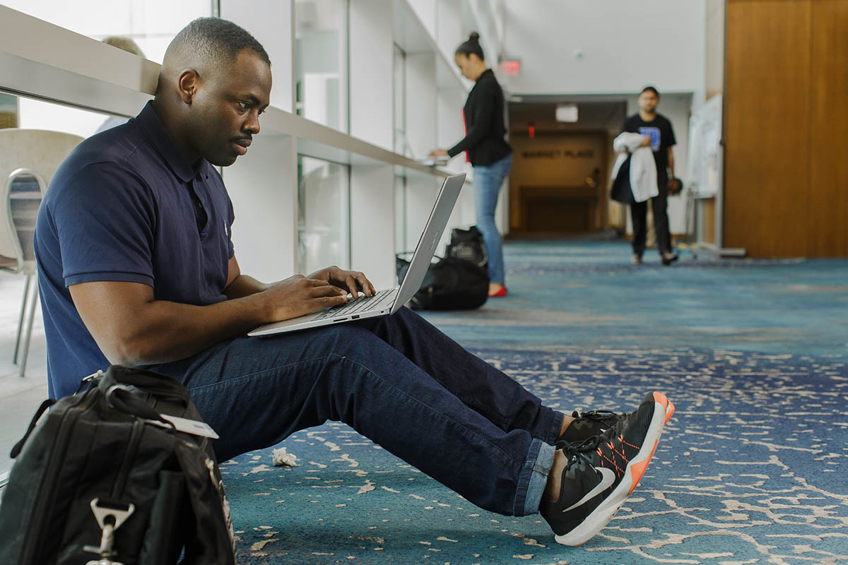 a student sitting in a hallway, working on his laptop; changing jobs during an executive MBA