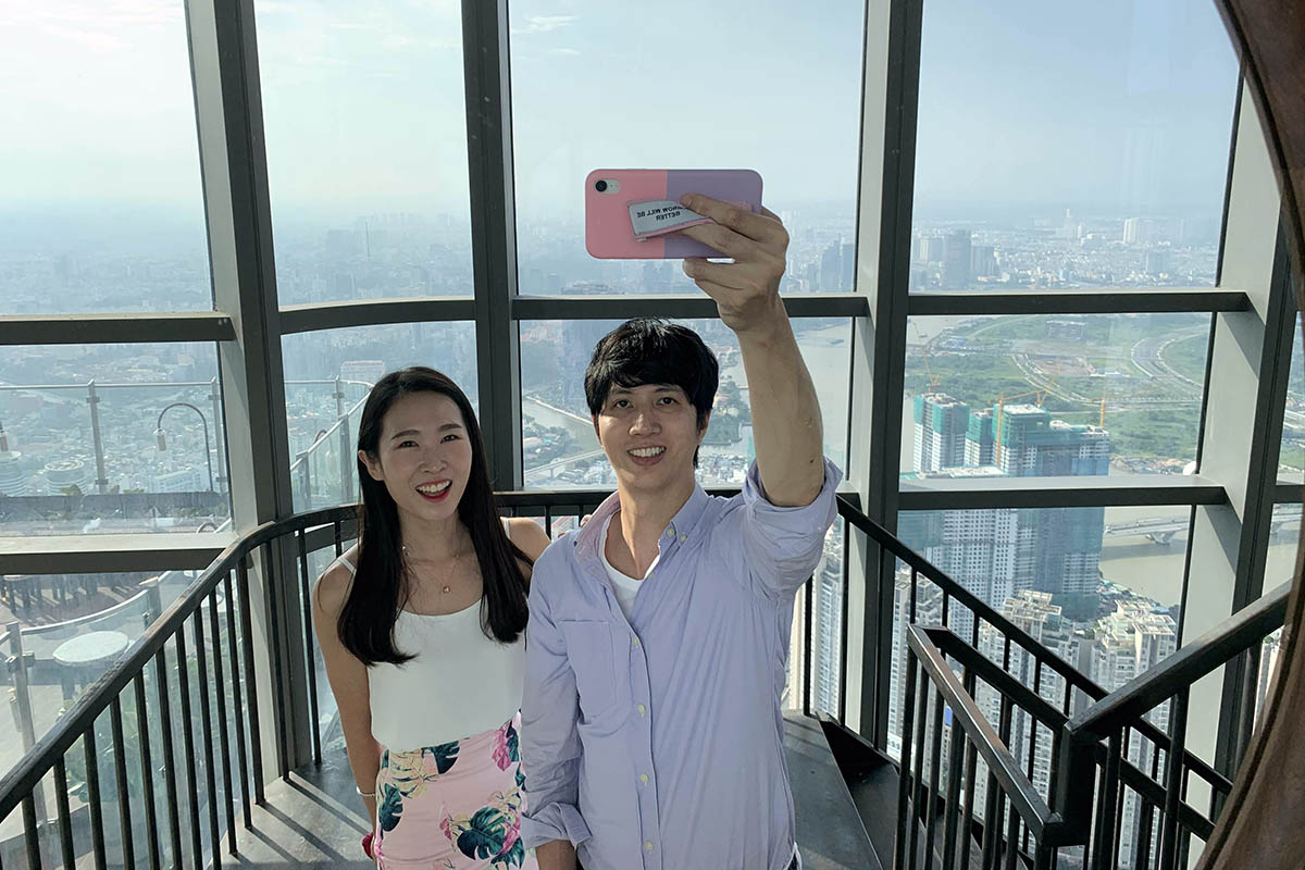 Chris and his wife taking a photos from a skyscraper looking out over the city below, lifetime relationships