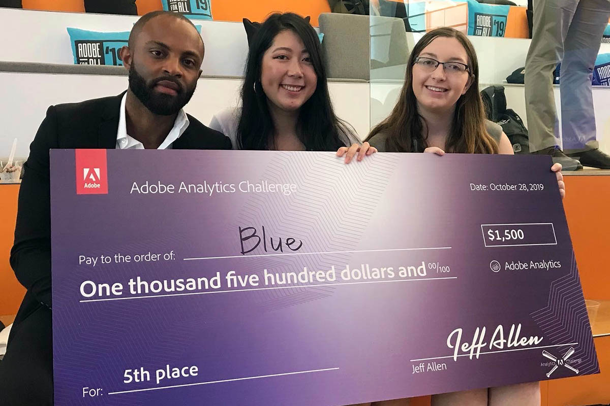 Jane and her two teammates holding up their giant check from the data challenge